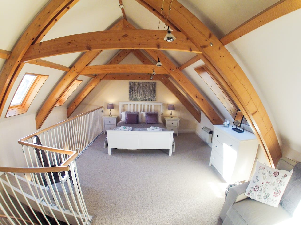 Light and open mezzanine bedroom with exposed beams, king size bed and double sofa bed