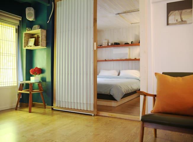 방1_ 두개의 방 중 큰방이에요           킹사이즈의 침대가 있고           벽걸이 에어컨이 있어요           일인용 쇼파도 놓여있어요   (침대가 방 왼편에 있었을때 모습)