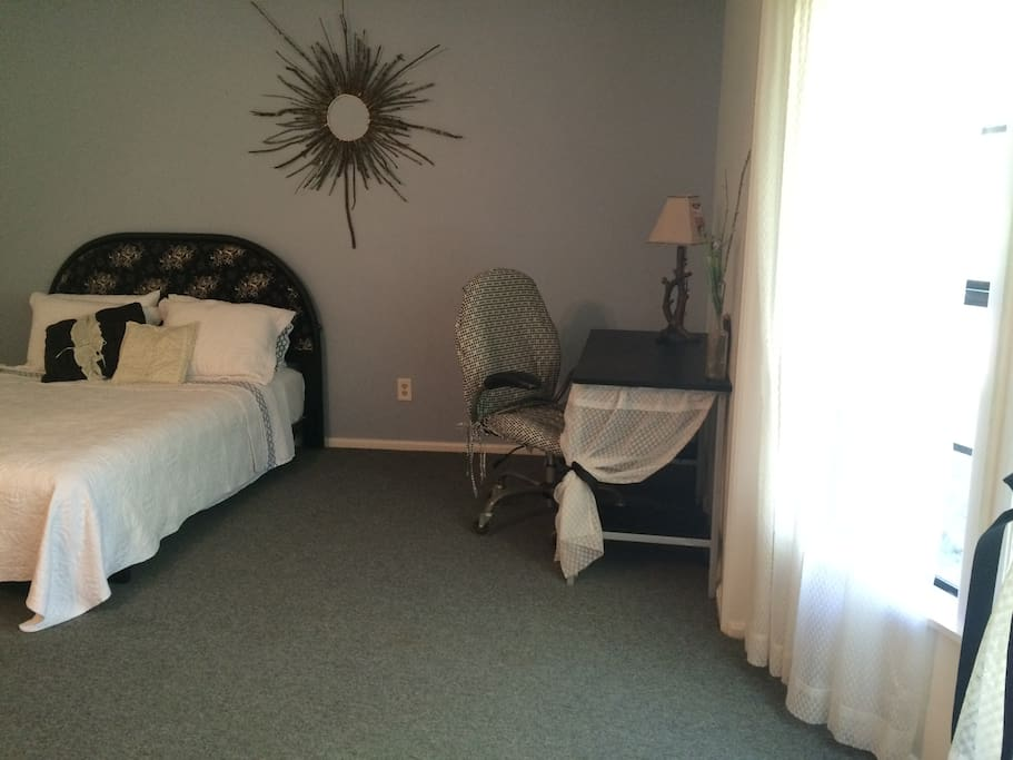 Main room includes a queen bed, writing desk, and a sleeper sofa.