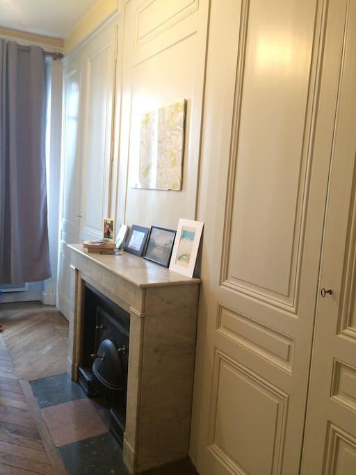 La chambre, vue d'un autre angle. La cheminée est décorative. Les rideaux sont occultants, et ne laissent que très peu passer la lumière.