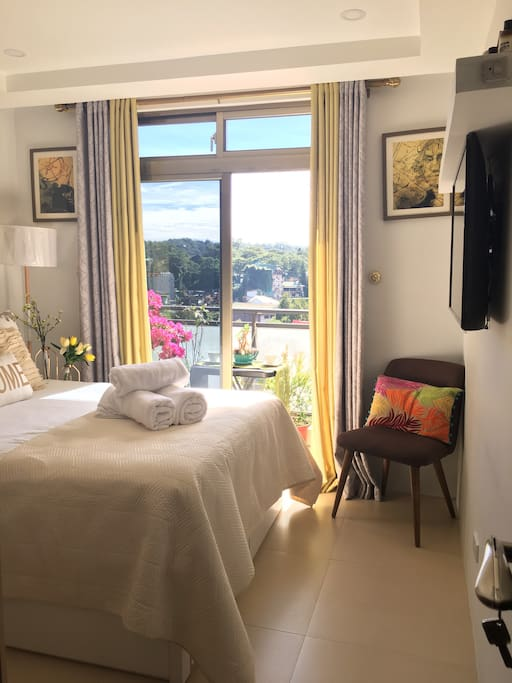 This is the master's bedroom equipped with an en-suite toilet and shower, freshly laundered linens and towels , 4K LG flat screen TV with Netflix and YouTube unlimited streaming. It has a balcony with table and chairs for you to enjoy a nice afternoon tea with a lovely and relaxing view.