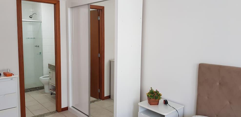 Suíte casal com armário e espelho na porta.