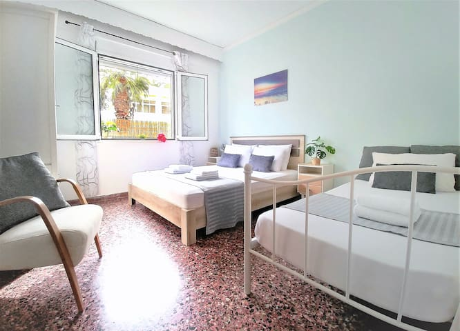 """This bedroom has 1 king-size bed and 1 single bed.  Enjoy the """"palm-tree view"""" outside!"""