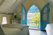 Master bedroom with beautiful original Gothic style windows. Sleeps three.