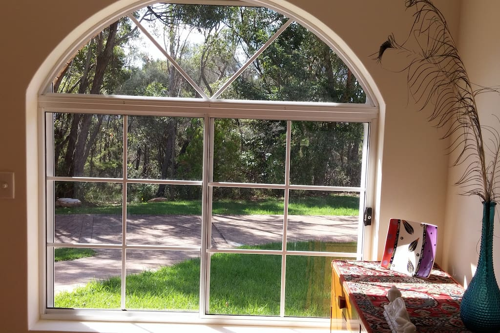 The front foyer arched window sets a framed view of the natural bushland scenery.