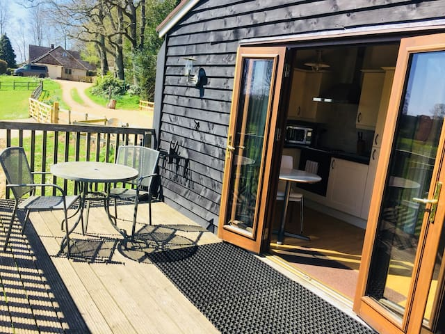 French doors opening onto a large sunny south facing elevated decking.