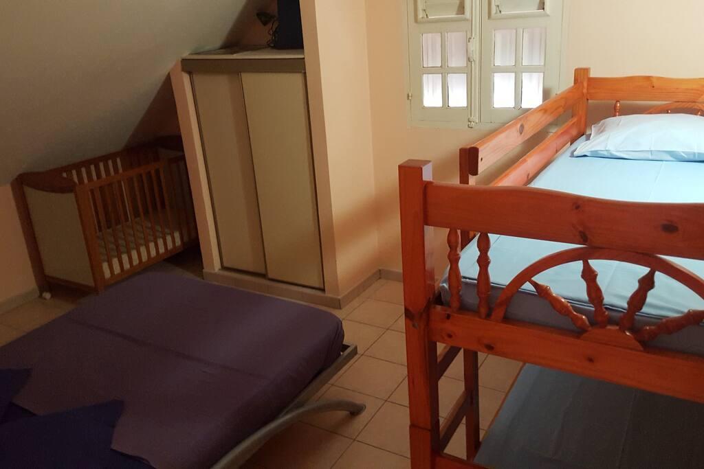 chambre étage avec une lit double et deux lits superposés