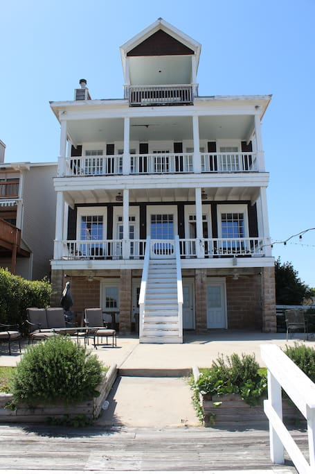 Back of the house with patio and two shared balconies.