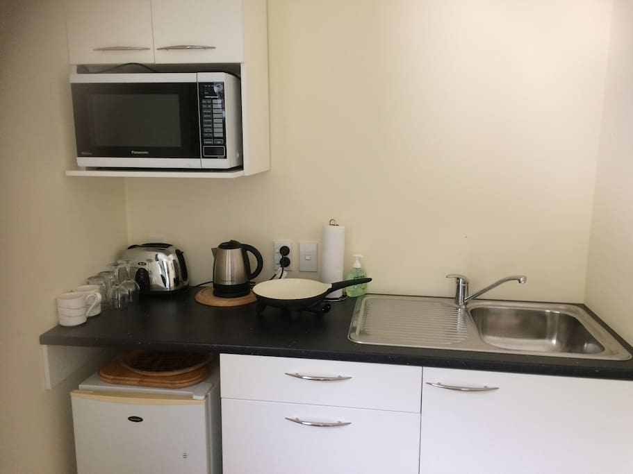 Kitchenette including fridge, toaster, electric jug, electric frypan, microwave.  Wine glasses, cutlery and crockery for two persons,