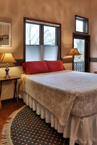 The queen bed is placed in front of the casement windows. Furniture gets moved around so it may be in another location when you arrive.