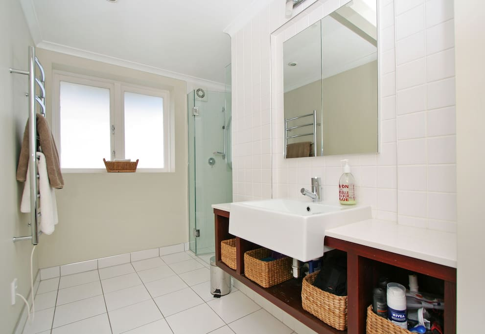 Bright, large tiled shower and bathroom with heated towel rail and complimentary soap, shampoo and conditioner.