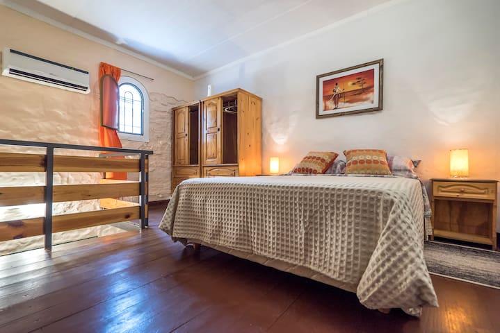 El dormitorio se encuentra en la parte alta del loft. Cuenta con una cama Queen de 160, TV, un Sillon, espejo y  un armario.
