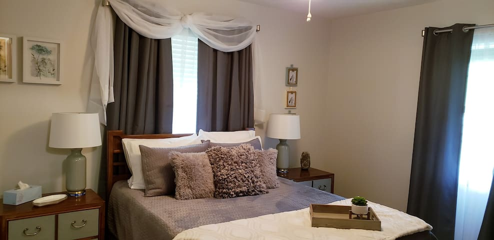 An ample bedroom with room darkening shades and curtains, a comfy queen bed, and a 3 speed ceiling fan make for a great night's sleep!