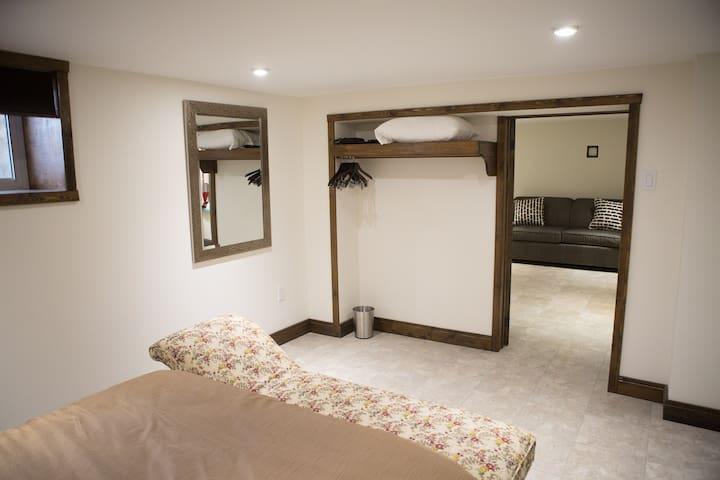 Bedroom 4 | rear basement bedroom . queen bed . chaise . tv