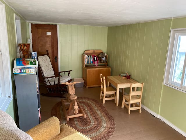 Back 4 season porch. This shows a small play area with books, games, child's table/chairs.