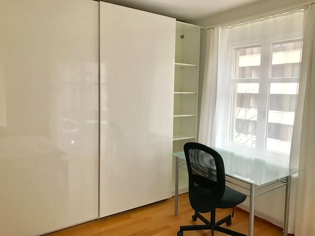 The room has a cabinet and a comfortable desk with an office chair.