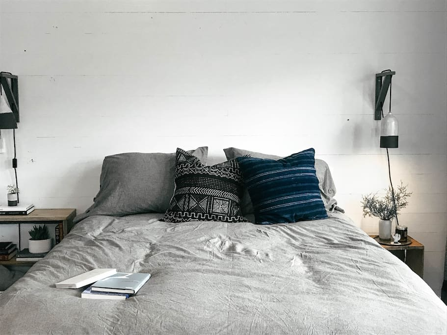 Handmade pendent lights flank each bed along with night stands stacked with good books to read.