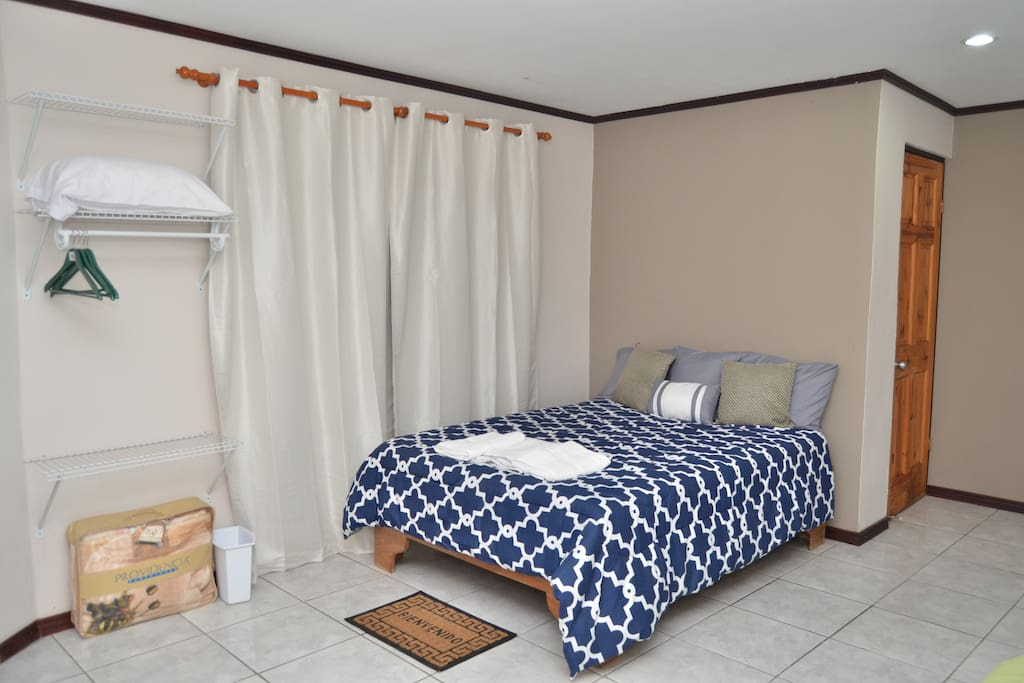 View of the main bed perfect for two people. The wood door you see at the back is the bathroom. We offer you: hangers, extra pillow, blanket & towels.
