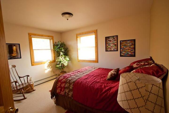 """Main floor """"leaf and brick"""" bedroom with a queen bed."""