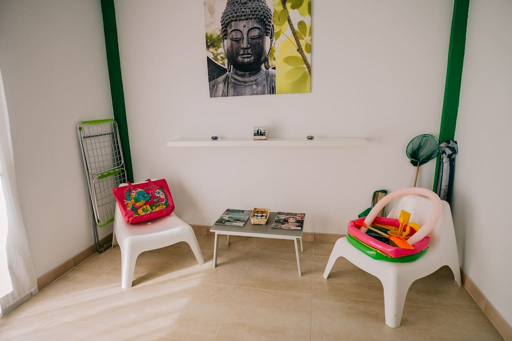 The green zen corner with beach toys and beach bag.