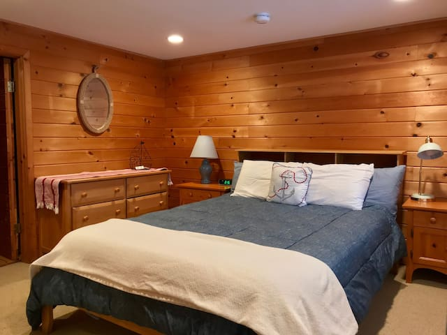 Queen-sized bed with memory-foam mattress includes 2 king-sized pillows and 2 standard pillows. Clock and brass gooseneck lamp both have USB ports. Dresser has 6 drawers. Extra pillows and blankets are stored in the closet.