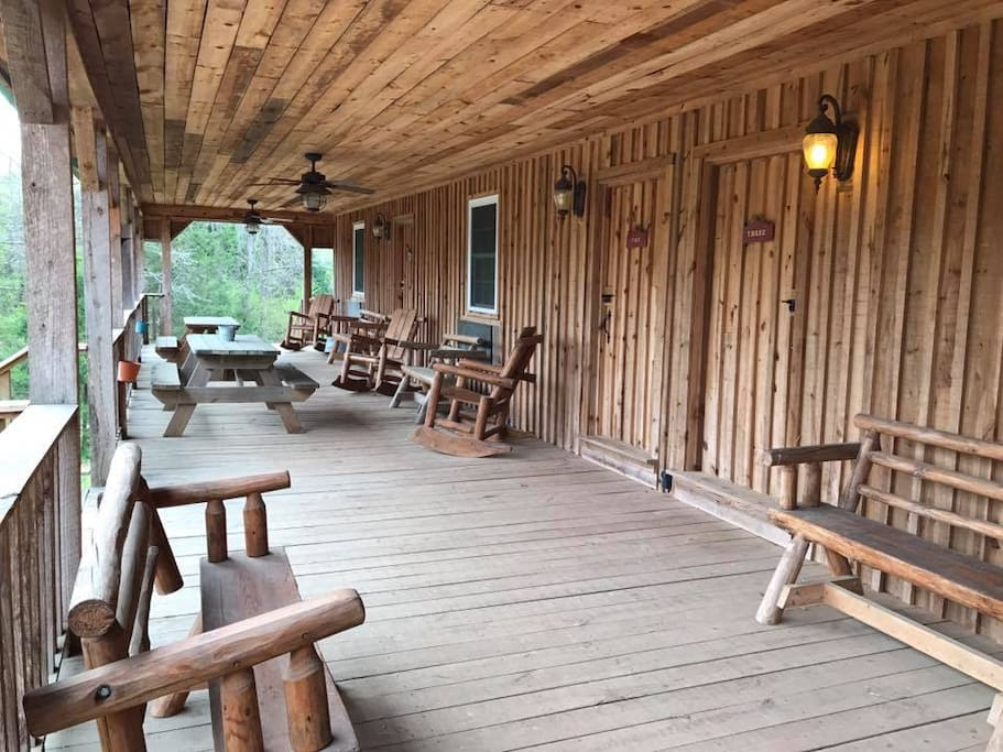 A very spacious porch is shared among the 4 individual cabin rooms. Each room containing their own bathroom, shower, 2 queen beds, table, closet, mini fridge, microwave, sink, coffee pot, heat, and air.