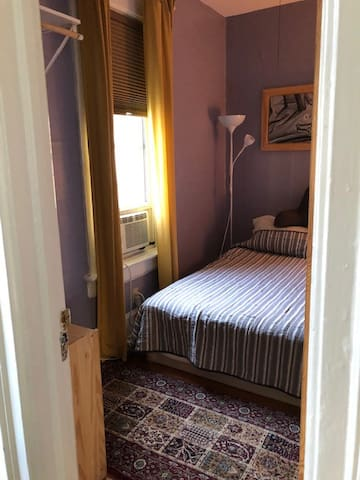 Same purple bedroom with big queen, summer scene with airconditioner and light coming in.