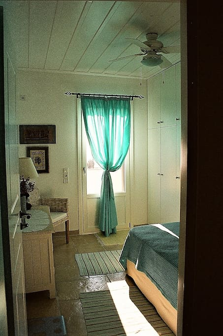Bright with sunshine and door leading out onto balcony.