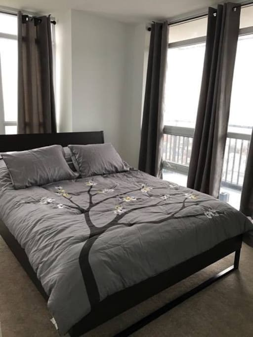 Master bedroom with a Queen bed. The big windows set a great view and the dark curtains can be closed for privacy.