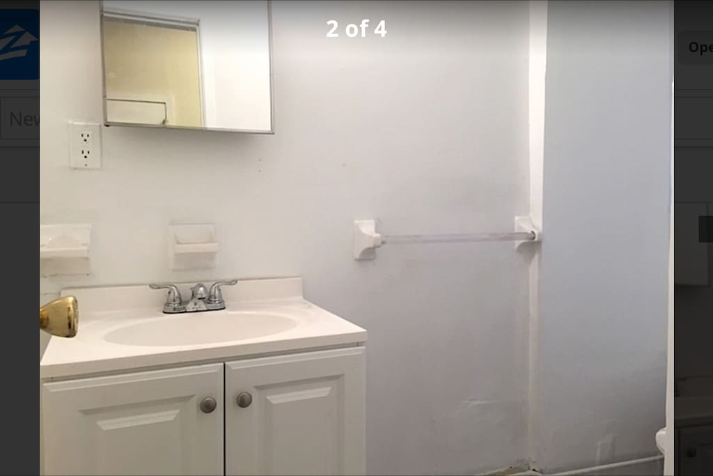 white bathroom with sink, mirror, toilet, and shower/tub.