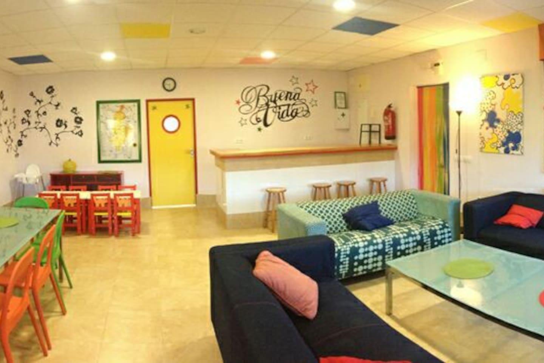 Salon comedor, 4 ambientes: corro de sofas, mesa grande, mesa niños, bar.