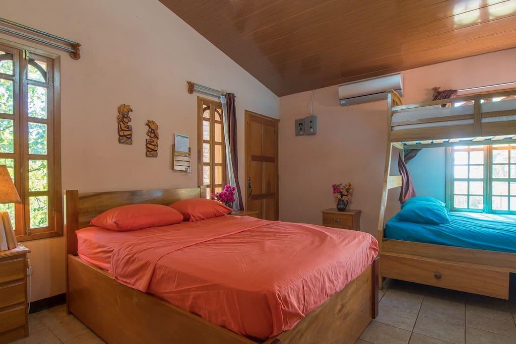 Una habitacion con dos camas matrimoniales, una cama unipersonal y un baño privado. Duermen 5 personas.