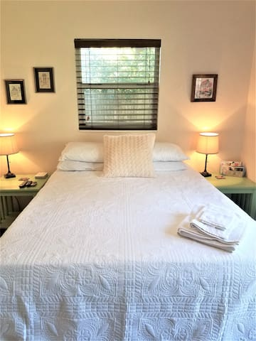 A view of your private room, featuring Tempurpedic queen-size bed, end tables, reading lights, charging station, & more.