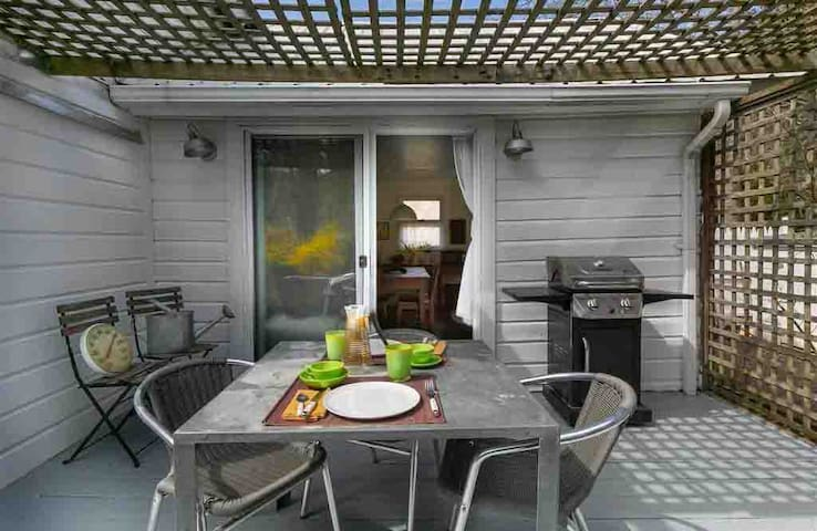 Deck off the kitchen with grill and seating.