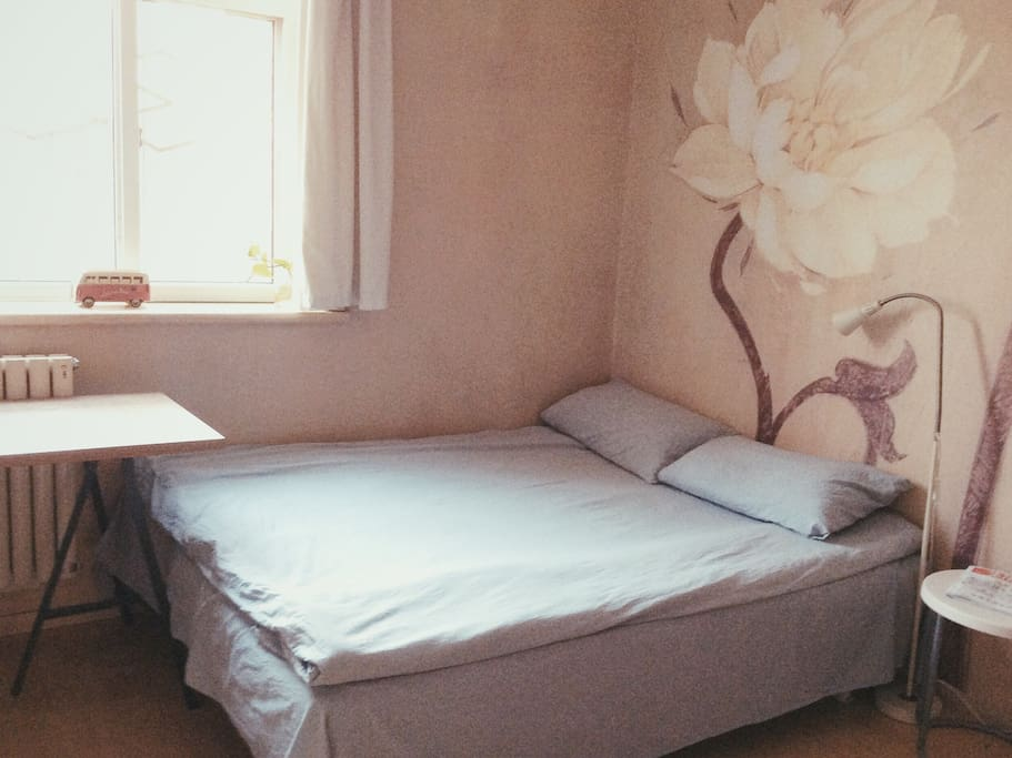 comfortable bed with beautiful flowers painting  wall