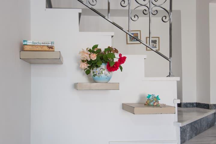 λεπτομέρεια τοίχου στον ενιαίο χώρο καθιστικού - κουζίνας. Η σκάλα οδηγεί στην κρεβατοκάμαρα