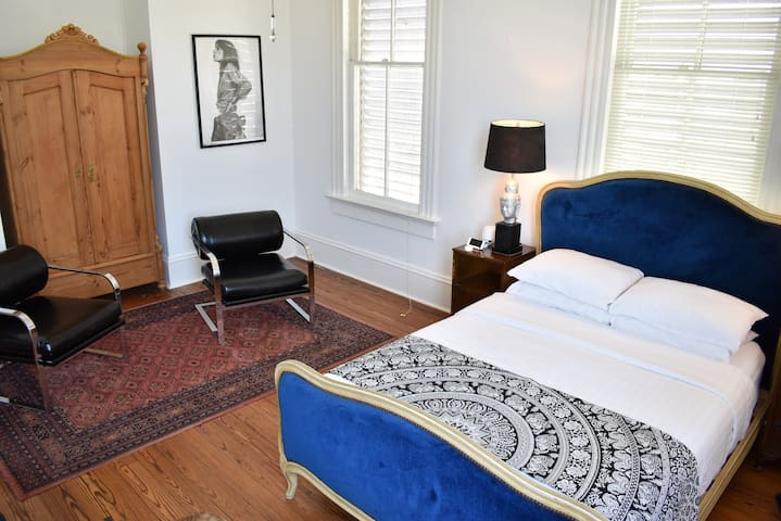 Room includes a double bed, two nightstands, a wardrobe, seating area, a dresser and a luggage rack.