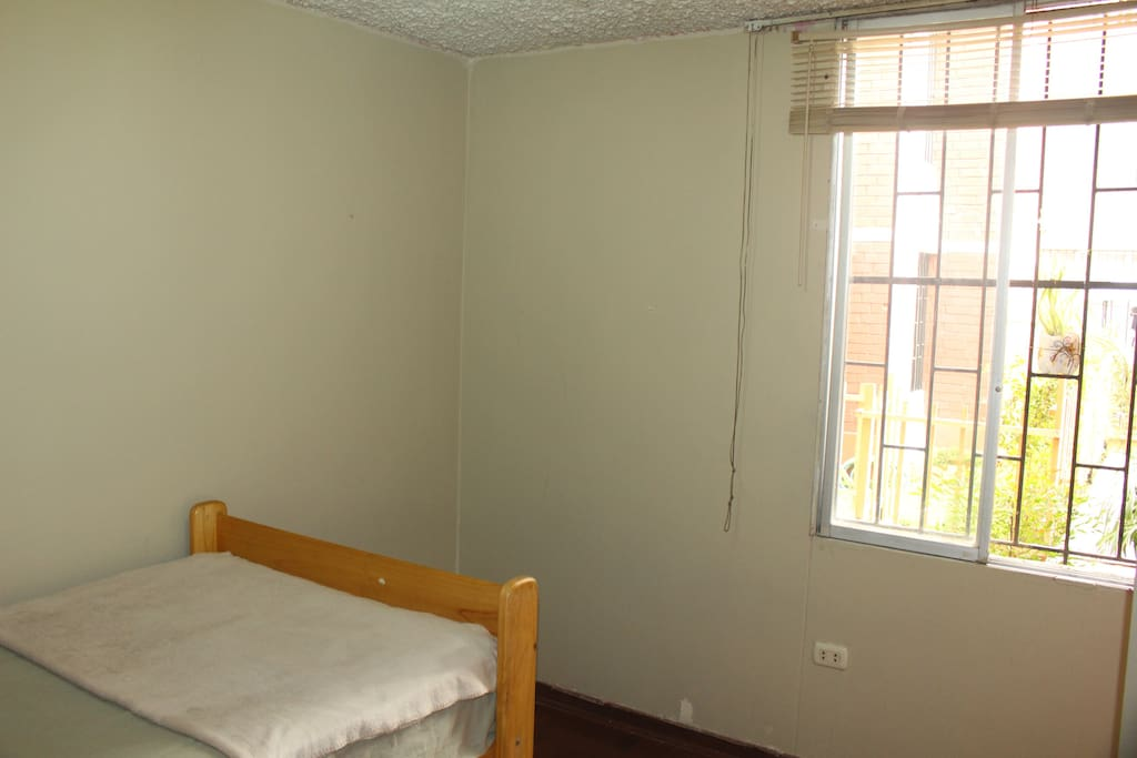 Habitación privada con una cama de una plaza, un closet, velador, mesa y dos sillas.