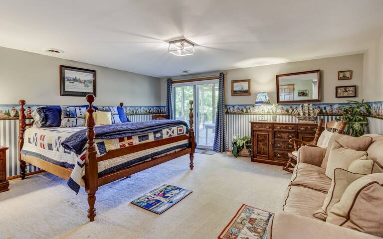 Maine bedroom features art and decor from the east coast. It has a comfortable couch, full closet and access to the lower porch area.