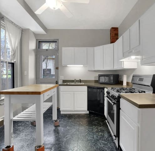 Well-equipped kitchen, leading to brick patio backyard.