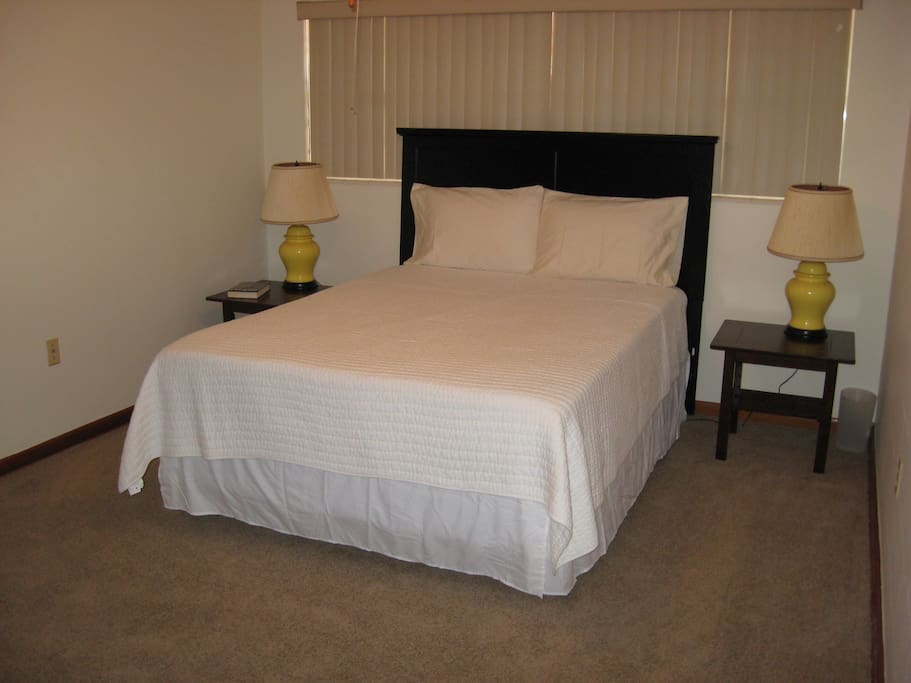 Bedroom with queen bed, two bedside tables and lamps.  Bed is high quality with firm support.