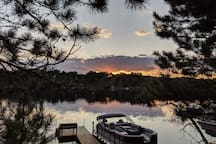 Cabins that face west are the best! Here's a classic sunset you can expect to see here on Long Lake. View from the yard overlooking the dock and the 2019 South Bay pontoon. Still evenings are common and reward you with mirror-like reflections.