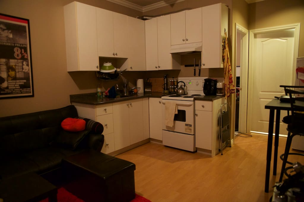 Kitchen with fridge, stove, utensils, microwave (not shown)