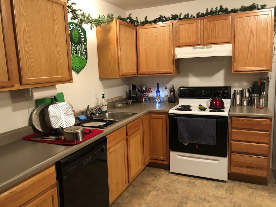 Kitchen with full size fridge, stove, and dishwasher.  Pots, pans, dishes, and tools for any cooking needs as well as a full spice set.