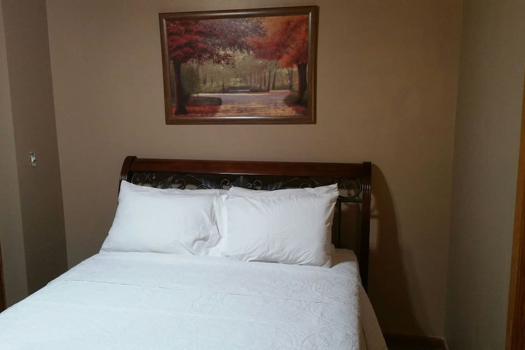 Queen size bed with fresh linen and comforter.