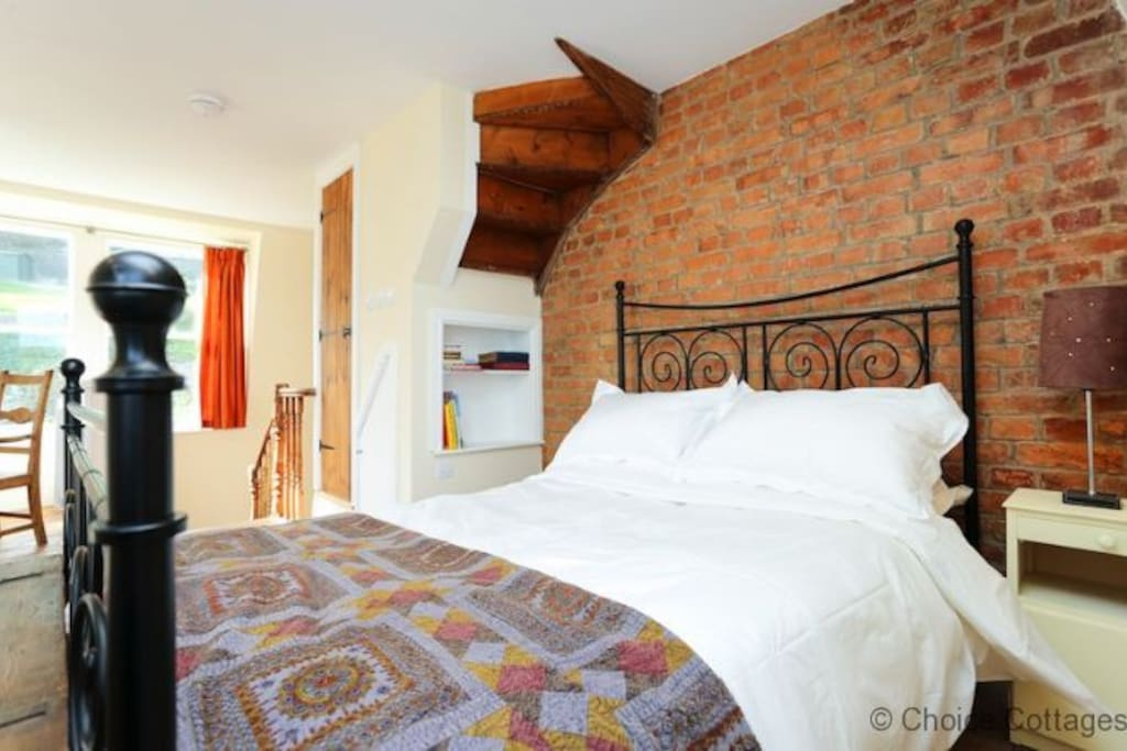 Large double Bed with beautiful brickwork wall & three windows with great views