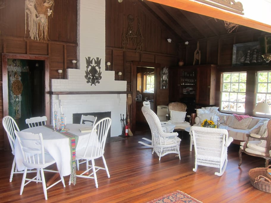 Cozy and wide open living room with dinner table. High dark wood vaulted dark wood ceiling.
