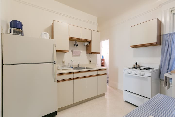 Kitchen showing full-size refrigerator, kitchen cabinetry, sink and stove