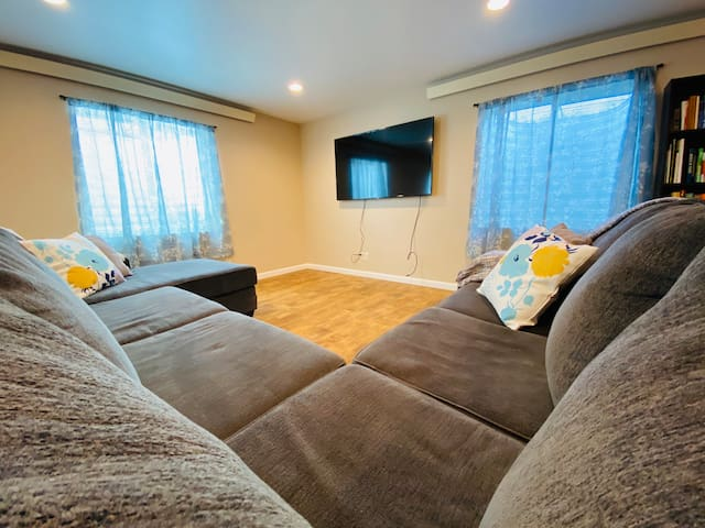 """Sitting area with large sectional and Samsung 65"""" Smart TV w/ HDMI"""