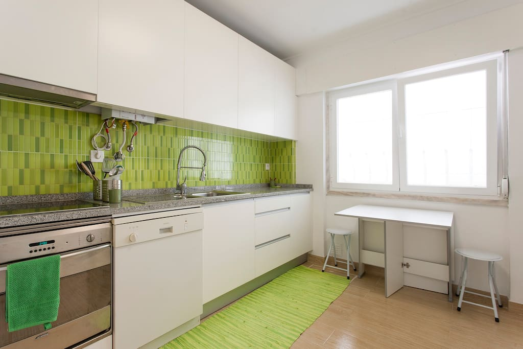 Fully equipped kitchen with an oven, stove, microwave, washing machine, laundry machine, drying machine and a table perfect for breakfast